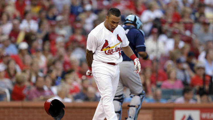 St. Louis Cardinals' Kolten Wong, front, slams down his helmet after striking out to end the third inning of a baseball game as Tampa Bay Rays catcher Jose Molina walks off the field Wednesday, July 23, 2014, in St. Louis. (AP Photo/Jeff Roberson)