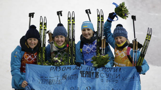 From left, Ukraine's relay team Vita Semerenko, Juliya Dzhyma, Olena Pidhrushna and Valj Semerenko pose with an Ukraine's flag, after winning the gold medal in the women's biathlon 4x6k relay at the 2014 Winter Olympics, Friday, Feb. 21, 2014, in Krasnaya Polyana, Russia. (AP Photo/Lee Jin-man)