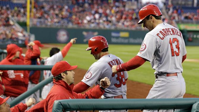 St. Louis Cardinals' Pete Kozma (38) and Matt Carpenter (13) celebrate with manager Mike Matheny, second from left, after scoring on a two-RBI double by Allen Craig during the third inning of a baseball game against the Washington Nationals at Nationals Park, Monday, April 22, 2013, in Washington. (AP Photo/Alex Brandon)