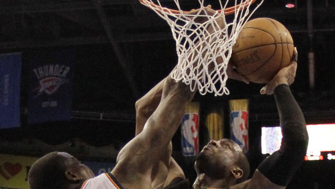 Miami Heat shooting guard Dwyane Wade shoots against Oklahoma City Thunder center Kendrick Perkins (5)during the second half at Game 2 of the NBA finals basketball series, Thursday, June 14, 2012, in Oklahoma City. (AP Photo/Jeff Roberson Pool)