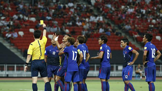 Referee awards a yellow card to Cambodia's Soeuy Visal during their 2018 World Cup Group E qualifying soccer match against Singapore at the National Stadium in Singapore