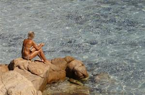 "A woman sits by the rocks at the Ramizzo beach in the so called ""Emerald Coast"" of the Sardinia island"