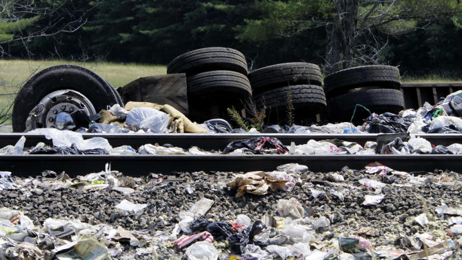 An overturned tractor-trailer is seen on the side of train tracks, Monday, July 11, 2011 in North Berwick, Maine, after an Amtrak train collided with it . Both were set on fire an official said and the truck driver was killed. Some of the train's 109 passengers were injured, but it's not clear how many or how seriously they were hurt, said an official.  The crash happened at about 11 a.m. in North Berwick, about 40 miles south of Portland. (AP Photo/Pat Wellenbach)