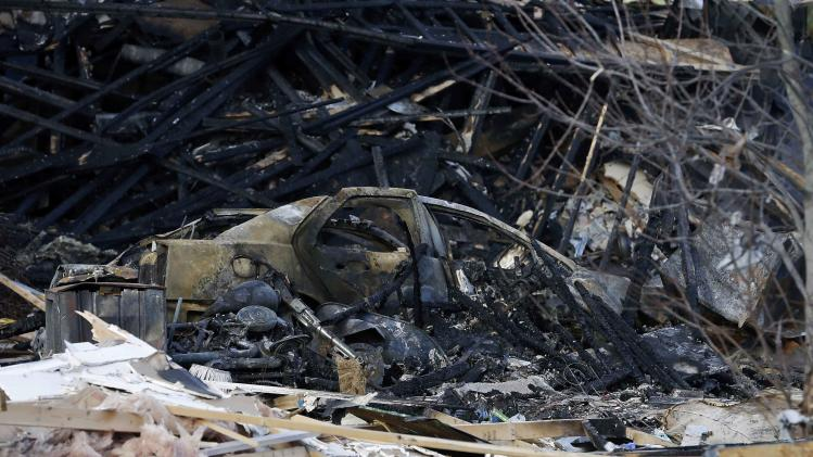 A burned car sits in a pile of debris at the site of a home explosion, Sunday, Nov. 11, 2012, in Indianapolis. Nearly three dozen homes were damaged or destroyed, and seven people were taken to a hospital with injuries, authorities said Sunday. The powerful nighttime blast shattered windows, crumpled walls and could be felt at least three miles away. (AP Photo/Darron Cummings)