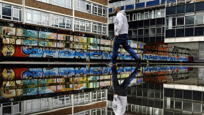 "File photo of a man passing graffiti near the Old Street roundabout dubbed ""Silicon Roundabout"" in London"