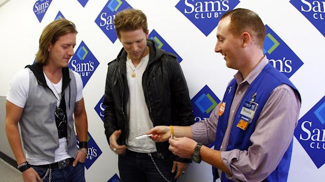 IMAGE DISTRIBUTED FOR GENERAL MILLS - Florida Georgia Line's Tyler Hubbard, left, and Brian Kelley receive membership cards at Sam's Club in support of Outnumber Hunger on Tuesday, March 19, 2013, in Nashville, Tenn.  (Photo by Wade Payne/Invision for General Mills/AP Images)
