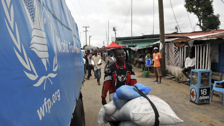 Resident of West Point neighbourhood, which has been quarantined following an outbreak of Ebola, pushes a wheelbarrow full of food rations from the United Nations World Food Programme in Monrovia