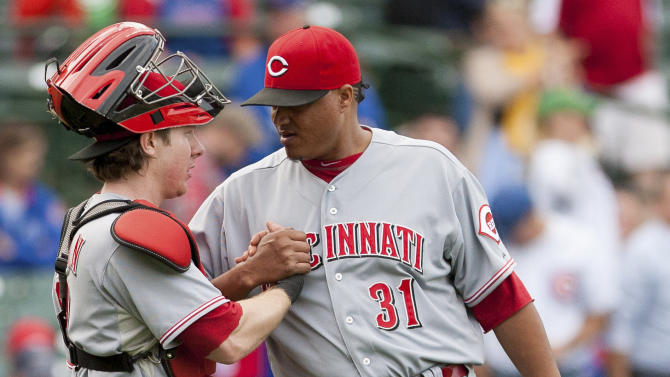 Cincinnati Reds pitcher Alfredo Simon, right, shakes hands with catcher Ryan Hanigan after beating the Chicago Cubs 5-3 in a baseball game in Chicago on Thursday, Sept. 20, 2012. (AP Photo/Charles Cherney)