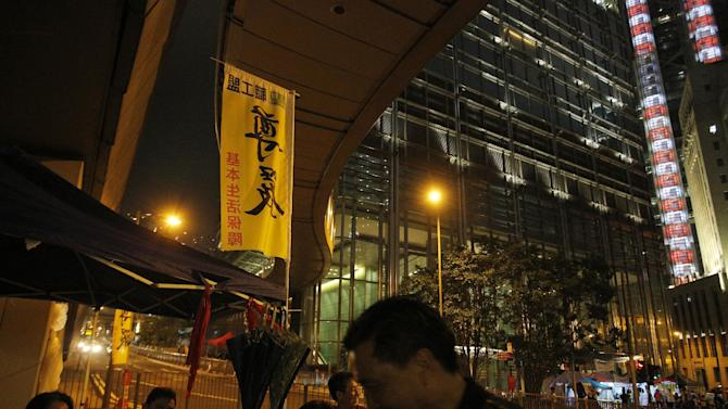 """A banner with chinese words """" Dignity """" is placed outside Hong Kong billionaire Li Ka-shing's headquarters, Cheung Kong Center during a protest in Hong Kong Monday, May 6, 2013. Hong Kong dockworkers have accepted a 9.8 percent pay increase, ending a 40-day strike that slowed traffic at one of the world's busiest ports. The workers settled their dispute late Monday by agreeing to the pay offer from four middleman contractors that provide staff to a container terminal operator controlled by Li Ka-shing. (AP Photo/Vincent Yu)"""