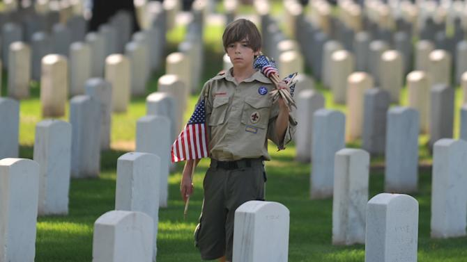 Matthew Russell, 11, from Memphis prepares to place American flags at the headstones of veterans during the Memorial Day observance ceremony at the Memphis National Cemetery in Memphis, Tenn. Saturday, May 26, 2012. For 29 years members of the Boy Scouts, Girl Scouts and American Heritage Girls have placed flags on the 42,000 graves at the Memphis National Cemetery during a ceremony honoring veterans for the Memorial Day Celebration.(AP Photo/The Commercial Appeal, Chris Desmond)