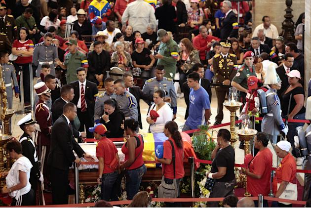 In this photo released by Miraflores Press Office,  mourners walk beside the coffin  containing the body of  Venezuela's late President Hugo Chavez on display during his wake at a military academy whe