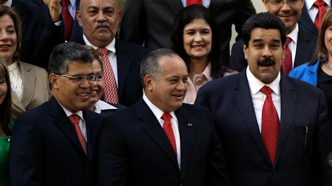 Venezuela's Vice President Nicolas Maduro, right, Disodado Cabello, center, President of Venezuela's National Assembly and newly designated Venezuela's Foreign Minister Elias Jaua greet supporters after attending the state-of-the-nation address in Caracas, Venezuela, Tuesday, Jan. 15, 2013. Maduro submitted the report in writing from ailing President Hugo Chavez, who is receiving treatment in Cuba after undergoing his fourth cancer surgery. Opposition politicians had argued that lawmakers should have postponed the annual speech because Chavez was supposed to deliver it. (AP Photo/Fernando Llano)