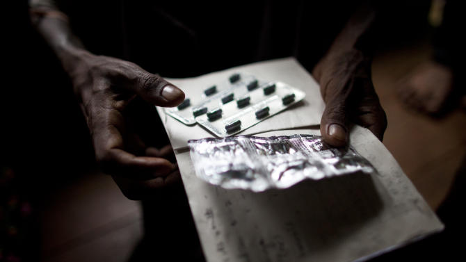 In this Sept. 1, 2012 photo, an HIV patient holds pills for his stomach ache and diarrhea at an HIV/AIDS center on the outskirts of Yangon, Myanmar. Following a half century of military rule, care for HIV/AIDS patients in Myanmar lags behind other countries. Half of the estimated 240,000 people living with the disease are going without treatment and 18,000 are dying from it every year. (AP Photo/Alexander F. Yuan)