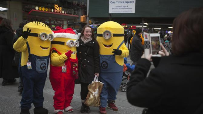 A woman poses for a photo with people dressed up as Minion characters in Times Square in New York