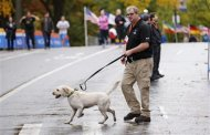 A security guard and bomb sniffing dog patrol the area near the finish line of the New York City Marathon in New York's Central Park November 1, 2013. REUTERS/Mike Segar