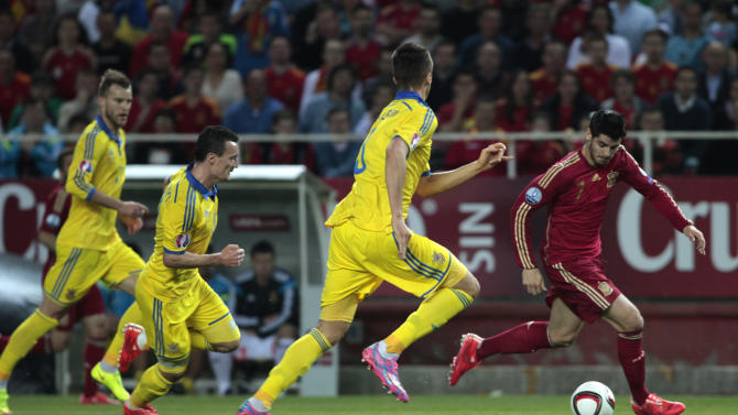 Spain's Alvaro Morata fights for the ball followed by Ukraine's Yevhen Khacheridi, left, during the Euro 2016 qualifying soccer match between Spain and Ukraine, at the Ramon Sanchez Pizjuan stadium, in Seville, Spain, on Friday, March. 27, 2015. (AP Photo/Angel Fernandez)
