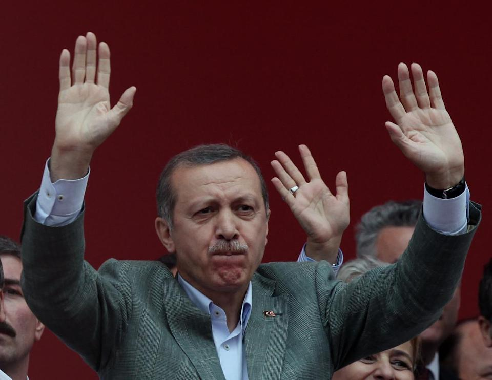 Turkish Prime Minister Recep Tayyip Erdogan salutes supporters during a party rally outside Ankara, Turkey, Saturday, June 15, 2013. Erdogan said Friday he has asked a small delegation of protesters to convince those occupying a park to withdraw, adding that he is hopeful their protest action would end soon.(AP Photo/Burhan Ozbilici)