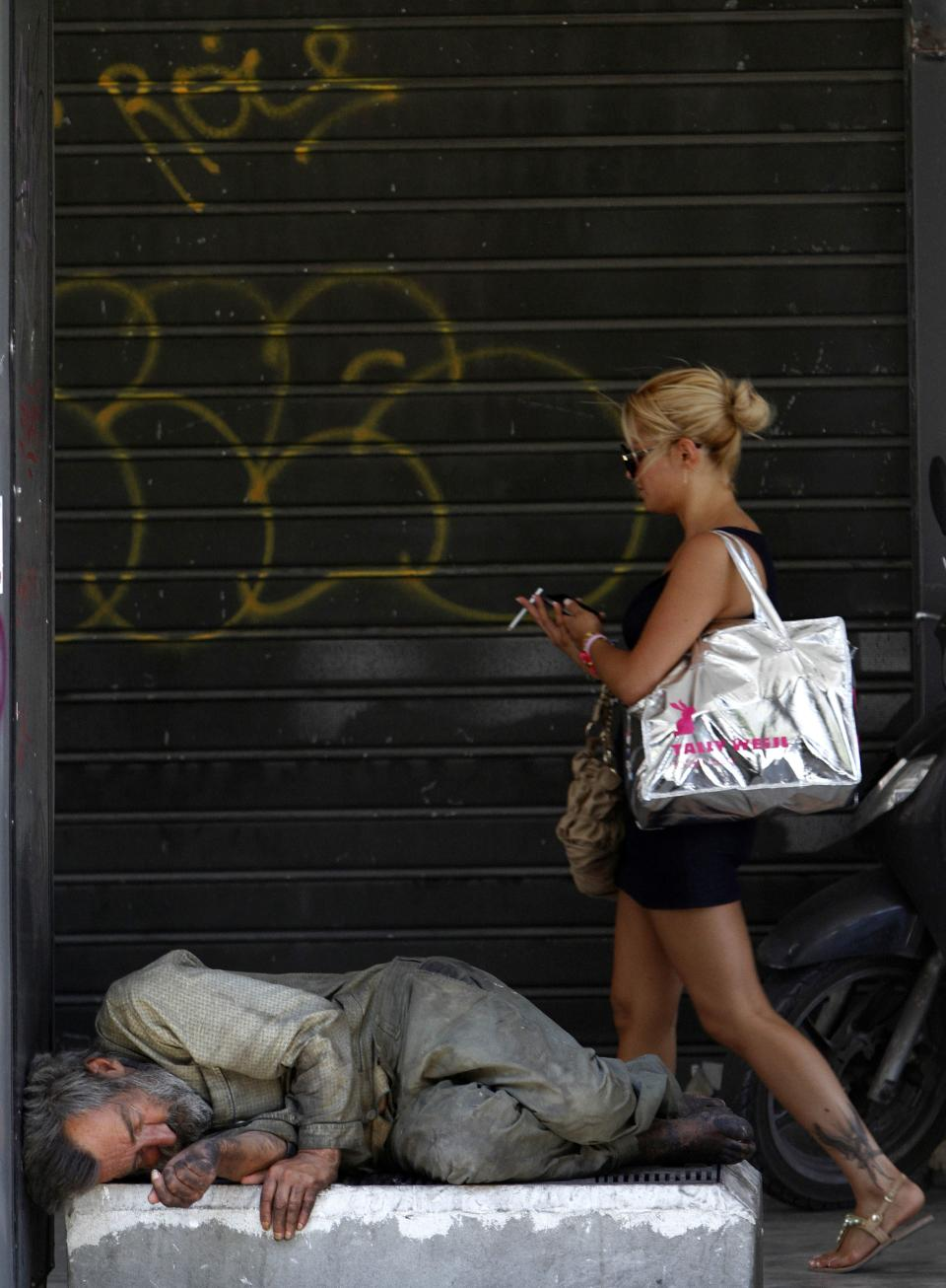 A homeless man sleeps on the ground as a woman passes by in central Athens, Saturday, June 16, 2012. Greeks cast their ballots this Sunday for the second time in six weeks, after May 6 elections left no party with enough seats in Parliament to form a government and coalition talks collapsed.  (AP Photo/Petros Karadjias)