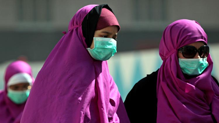 In this photo taken Tuesday May, 13, 2014, Muslim pilgrims wear surgical masks to prevent infection from respiratory virus known as the Middle East respiratory syndrome (MERS) in the holy city of Mecca, Saudi Arabia. Officials in Saudi Arabia are raising alarm that the kingdom is not doing enough to prevent Mecca from becoming a route for exporting an often deadly respiratory virus as millions of Muslims from around the world converge on the city to perform pilgrimage at Islam's holiest site. (AP Photo/Hasan Jamali)