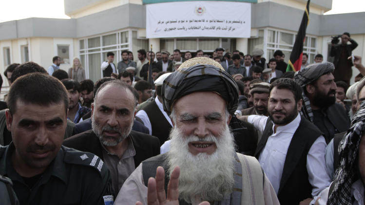 Abdul Rab Rasoul Sayyaf, an influential lawmaker and religious scholar, waves at his supporters after registering his candidacy in next year's presidential election in Kabul, Afghanistan, Thursday, Oct. 3, 2013. Another former warlord, Ismail Khan, who formerly served as energy and water minister, said he will run for Sayyaf's first vice-president in the April 5 vote. (AP Photo/Rahmat Gul)