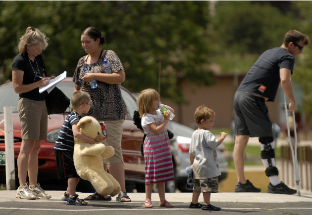 Evacuees of the Waldo Canyon Fire are assisted by a volunteers from the Red Cross at the Cheyenne Mountain High School evacuation center on Wednesday, June 27, 2012,  in Colorado Springs, Colo. The wi