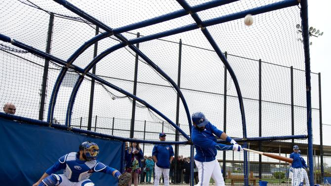 Toronto Blue Jays slugger Jose Bautista hits as Blue Jays catcher Russell Martin catches during baseball spring training in Dunedin, Fla., on Friday, Feb. 27, 2015. ()AP Photo/The Canadian Press, Nathan Denette)