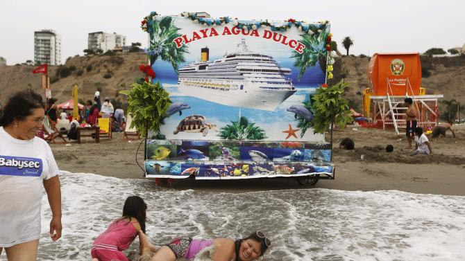 People enjoy the beach near a photography backdrop on a summer's day at Agua Dulce beach in Lima