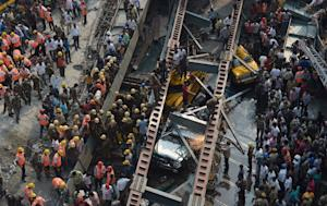 Rescue workers and volunteers try to free people trapped…