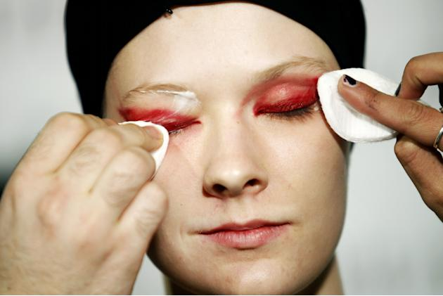 A model gets her eye make-up removed backstage during the ModaLisboa fashion week, in Lisbon, Portugal Sunday, March 9, 2014. (AP Photo/Francisco Seco)