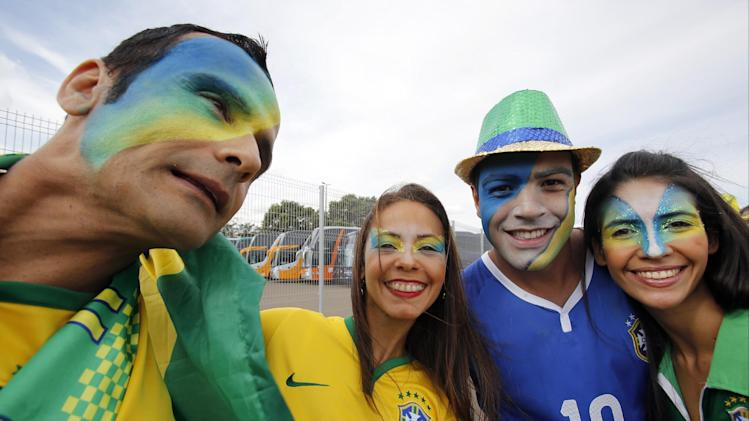 Soccer fans have their faces painted in the Brazilian colors as they arrive for the group A World Cup soccer match between Cameroon and Brazil at the Estadio Nacional in Brasilia, Brazil, Monday, June 23, 2014. (AP Photo/Dolores Ochoa)
