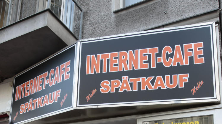 People enter the internet cafe where Luka Rocco Magnottahe was recognize in the district of Neukoelln in Berlin, Germany, Monday, June 4, 2012. Kadir Anlayisli who works in the after hours liqueur and tobacco shop with internet cafe, called a police man from outside saying he recognized the suspect person. Magnotta is wanted by Canadian authorities on first-degree murder and other charges. He is suspected of killing Jun Lin a 33-year-old Chinese university student he dated, and mailing Lin's body parts to Canadian political parties. (AP Photo/Markus Schreiber)