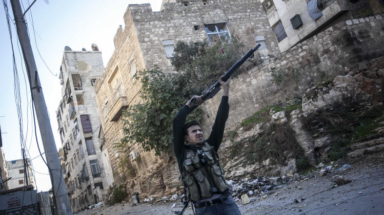 In this Wednesday, Nov. 14, 2012 photo, a Syrian rebel fighter aims at Syrian government forces during skirmishes in Aleppo, Syria. (AP Photo/Narciso Contreras)