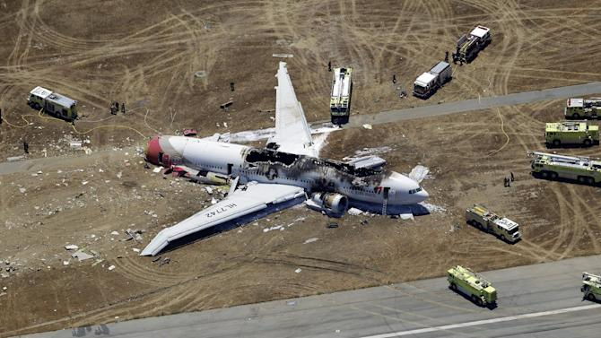 FILE - This July 6, 2013, file photo shows the wreckage of Asiana Flight 214 on the ground after it crashed at the San Francisco International Airport, in San Francisco. When the courts have to figure compensation for people aboard Flight 214, the potential payouts will probably be vastly different for Americans and passengers from other countries. A pact is likely to close U.S. courts to many foreigners and force them to pursue their claims in Asia and elsewhere, where lawsuits are rarer, harder to win (AP Photo/Marcio Jose Sanchez, File)