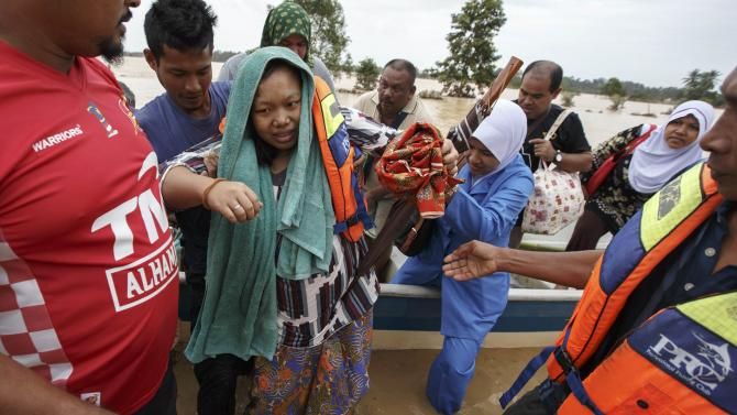 A pregnant woman is evacuated from her home by rescue workers as she is taken to a hospital on the outskirts of Kota Bharu