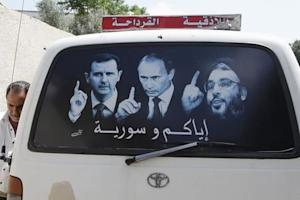 A poster showing Syrian President Assad, Russian President…