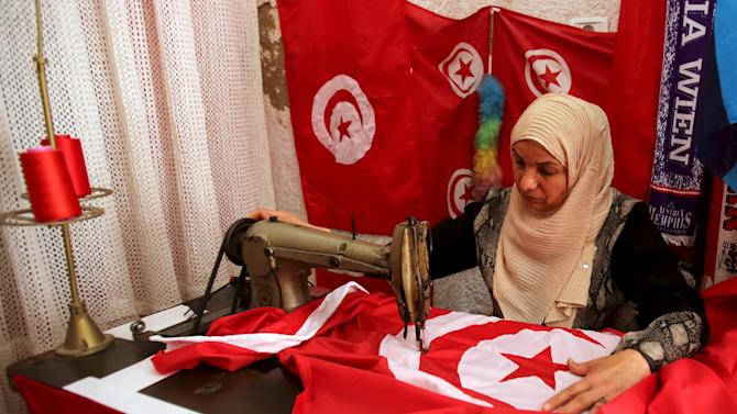 A worker sews Tunisian national flags in a workshop in Tunis