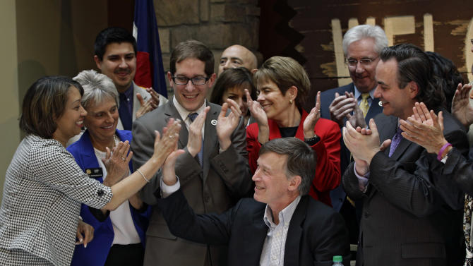 Colorado Gov. John Hickenlooper, center, exchanges high-fives with members of the State Legislature after he signs the Civil Unions Act into law at the Colorado History Museum in Denver, Colo., on Thursday, March 21, 2013. (AP Photo/Brennan Linsley)