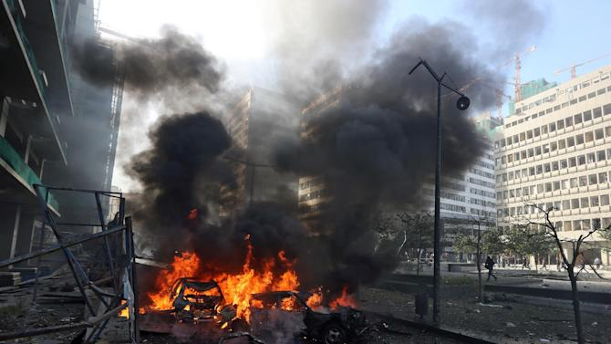 Flames blaze from vehicles at the scene of an explosion in Beirut, Lebanon, Friday, Dec. 27, 2013. A strong explosion has shaken the Lebanese capital, sending black smoke billowing from the center of Beirut. The blast went off a few hundred meters (yards) from the government headquarters and parliament building. (AP Photo/Bilal Hussein)