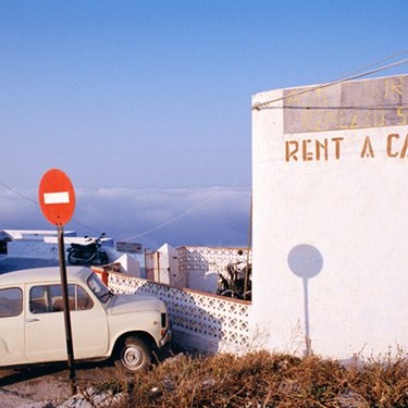 An-older-style-car-parked-outside-of-a-building-with-a-sign-reading-rent-a-car-in-greece_web