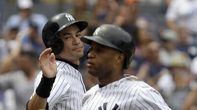 New York Yankees' Ichiro Suzuki, left, greets Robinson Cano after they scored on a single by Lyle Overbay during the fifth inning of a baseball game at Yankee Stadium Thursday, July 11, 2013 in New York. (AP Photo/Seth Wenig)