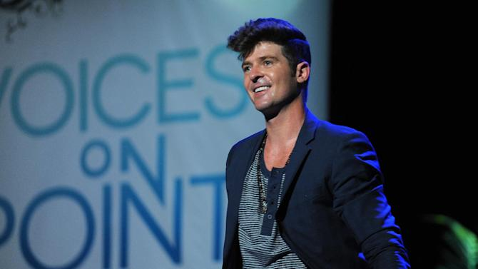 """FILE - In this Sept. 15, 2012 publicity photo provided by the Point Foundation, Robin Thicke performs at """"Voices On Point"""" Concert & Gala held at The Wiltern theatre, in Los Angeles. Thicke originally didn't plan to release the unrated version of his music video for the song """"Blurred Lines,"""" which features nude models prowling around him and rappers Pharrell and T.I. Thicke's unrated video hit the Web on Tuesday, March 26, 2013, and so far it has more than 700,000 views. (AP Photo/Point Foundation, Colin Young-Wolff, File)"""