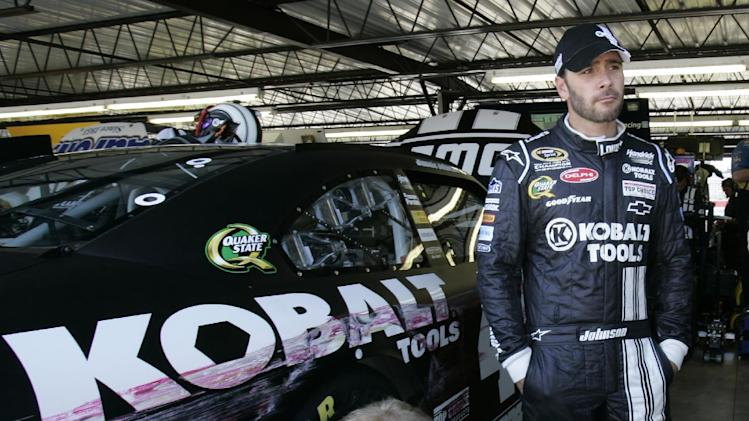 CORRECTS RACE DAY TO SATURDAY, NOT SUNDAY - Driver Jimmie Johnson look on as his crew work to repair his car after hitting the wall during practice for Saturday's NASCAR Sprint Cup Series auto race at Darlington Raceway, Friday, May 11, 2012, in Darlington, S.C. (AP Photo/Mary Ann Chastain)