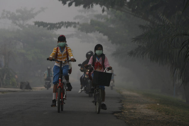 Students cycle through the haze-blanketed town of Sampit, in Indonesia's Central Kalimantan province