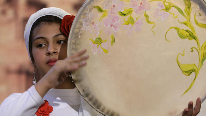 An Iranian Zoroastrian girl, plays Daf, a large-sized tambourine, during Sadeh festival, an ancient Zoroastrians' feast celebrating the creation of fire, outside the capital of Tehran, Iran, Tuesday, Jan. 29, 2013.  Followers of Iran's minority Zoroastrian religion gathered after sunset to mark Sadeh, an ancient mid-winter feast dating to Iran's pre-Islamic past that is also drawing new interest from Muslims. (AP Photo/Vahid Salemi)