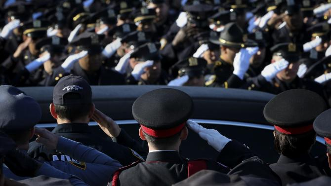 Law enforcement officers salute as the hearse carrying the casket containing the body of slain New York Police Department (NYPD) officer Rafael Ramos departs the Christ Tabernacle Church to it's final resting place in the Queens borough of New York