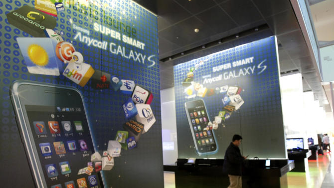 A visitor walks by signs advertising Samsung Electronics Co's smart phone in a showroom at Samsung Electronics Co. headquarters in Seoul, South Korea, Friday, Jan. 7, 2011. Samsung Electronics forecast Friday that both sales and operating profit rose to record highs in 2010 despite sluggishness at the end of the year amid lower prices for televisions and semiconductors. (AP Photo/Ahn Young-joon)