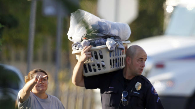 "Alma Cardona, left, directs an Aurora police officer carrying some of her items, after she was allowed in to get some belongings from her home near the apartment of alleged gunman James Holmes Friday, July 20, 2012 in Aurora, Colo. Authorities report that 12 died and more than three dozen people were shot during an assault at the theatre during a midnight premiere of ""The Dark Knight."" Colorado firefighters are monitoring the Aurora apartment building for gases in an effort to determine what chemicals they say 24-year-old James Holmes might have used to trap the place _ in case the materials go off.  (AP Photo/Alex Brandon)"