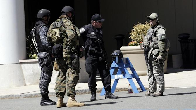 Officials in tactical gear stand guard behind a Boston Police Department barricade near the site of the Boston Marathon explosions, Wednesday, April 17, 2013, in Boston. The city continues to cope following Monday's explosions near the finish line of the marathon. (AP Photo/Julio Cortez)