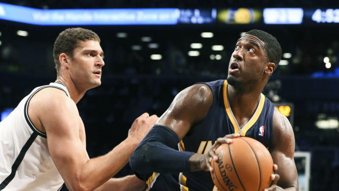 Indiana Pacers center Roy Hibbert (55) looks to shoot the ball against Brooklyn Nets center Brook Lopez (11) during the first half of an NBA basketball game against the Brooklyn Nets, Saturday, Nov. 9, 2013, at the Barclays Center in New York. (AP Photo/John Minchillo)