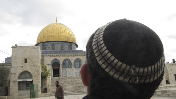 In this Monday, Dec. 9, 2013 photo, a Jewish man looks towards the Dome of the Rock in Jerusalem. The Jerusalem site, known to Muslims as the Noble Sanctuary and to Jews as the Temple Mount, is ground zero in the territorial and religious conflict between Israel and its Arab neighbors. Jewish visits to the politically sensitive compound are on the rise, and key Israeli lawmakers are lobbying to end a ban on Jewish prayer there. The hilltop site is so holy to Jews that they have traditionally refrained from praying there, congregating instead at the adjacent Western Wall. (AP Photo/Simone Camilli)